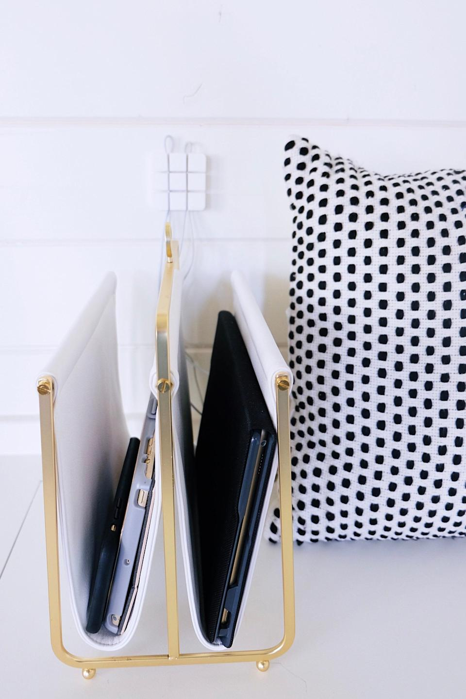 """Multiple devices lead to an abundance of charging cables, which is the ultimate eyesore. Shearer recommends creating a fashionable docking station to camouflage the clutter: """"One of our favorite methods is to repurpose a magazine rack to divide laptops, tablets, and phones, then add a multi-cable holder to keep the cords organized."""""""