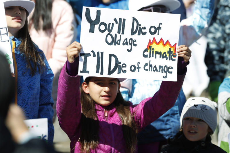 Ten-year-old Harper Phillips of Denver waves a placard as Swedish climate activist Greta Thunberg speaks to several thousand people at a climate strike rally Friday, Oct. 11, 2019, in Denver. The rally was staged in Denver's Civic Center Park. (AP Photo/David Zalubowski)