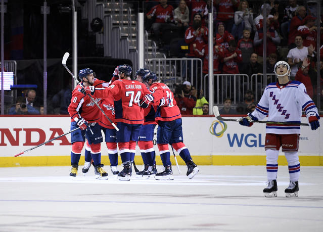 Washington Capitals left wing Alex Ovechkin (8), of Russia, celebrates his goal with defenseman John Carlson (74), center Nicklas Backstrom (19) and others as New York Rangers defenseman Neal Pionk skates by at right during the second period of an NHL hockey game, Wednesday, Oct. 17, 2018, in Washington. The Capitals won 4-3 in overtime. (AP Photo/Nick Wass)