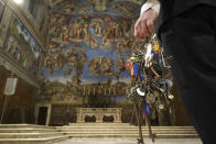 """Gianni Crea, the Vatican Museums chief """"Clavigero"""" keys keeper walks through the Sistine Chapel as he prepares to open the museum, at the Vatican, Monday, Feb. 1, 2021. The Vatican Museums reopened Monday to visitors after 88 days of shutdown following COVID-19 containment measures. (AP Photo/Andrew Medichini)"""