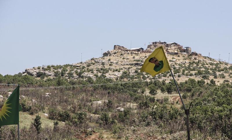 A Turkish army station is seen above a flag bearing the portrait of jailed Kurdish leader Abdullah Ocalan at a checkpoint manned by Kurdish protestors, in Lice, Diyarbakir province, eastern Turkey, on June 10, 2014