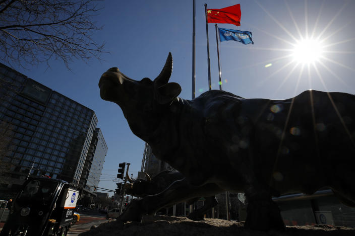A delivery worker ride his cart passes by the investment icon bull statue on display outside a bank in Beijing, Tuesday, March 10, 2020. Asian stock markets are taking a breather from recent declines. Several benchmarks gained more than 1% on Tuesday after New York futures reversed on news that President Donald Trump plans to ask Congress for a tax cut and other quick measures to ease the pain of the virus outbreak. (AP Photo/Andy Wong)