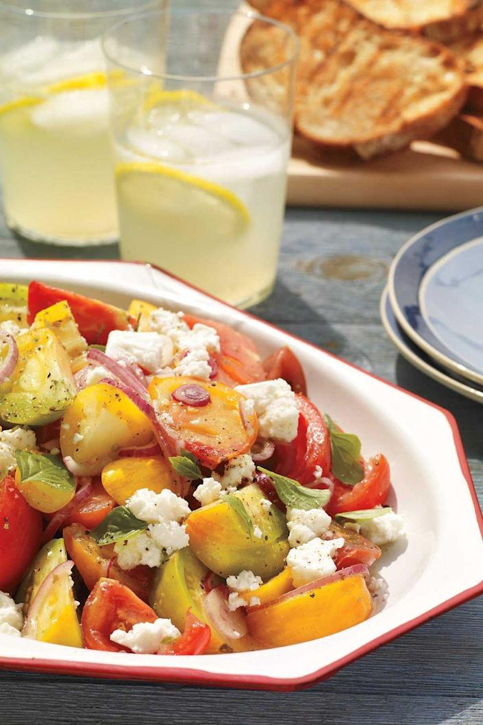 """<p>A salad of crumbled feta cheese, red onions, basil, and heirloom tomatoes is the perfect pairing for toasted semolina bread rubbed with garlic. </p><p><strong><u><em><a href="""" https://www.womansday.com/food-recipes/food-drinks/recipes/a11309/heirloom-tomato-salad-grilled-garlic-bread-recipe-122674/"""" rel=""""nofollow noopener"""" target=""""_blank"""" data-ylk=""""slk:Get the recipe for Heirloom Tomato Salad with Grilled Garlic Bread"""" class=""""link rapid-noclick-resp"""">Get the recipe for Heirloom Tomato Salad with Grilled Garlic Bread</a>.</em></u> </strong></p>"""