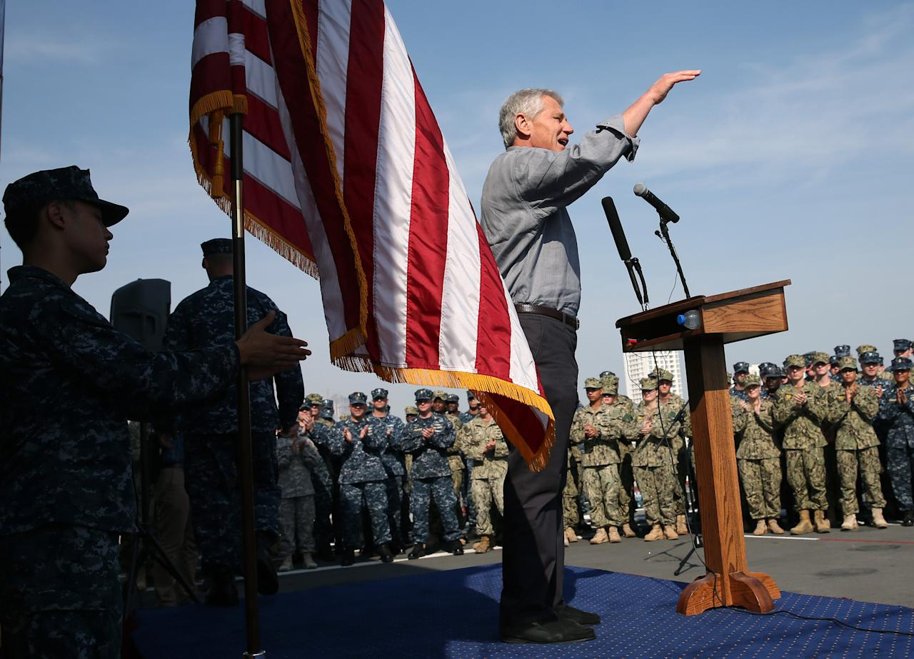 "U.S. Defense Secretary Chuck Hagel speaks to military service members aboard the USS Ponce in Manama, Bahrain, Friday, Dec. 6, 2013. Standing on the massive deck of the Navy's USS Ponce, Hagel said the U.S. is entering the new nuclear pact with Iran ""very clear eyed"" and it remains to be see whether Tehran is serious about keeping its development peaceful. (AP Photo by Mark Wilson, Pool)"
