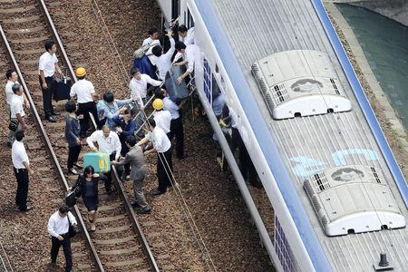 Passengers get off a train which operation was suspended after an earthquake in Takatsuki