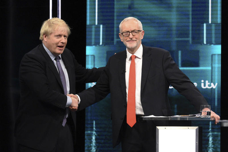 In this photo issued by ITV, Boris Johnson, left, and Jeremy Corbyn, right, shake hands during their election head-to-head debate live on TV, in Manchester, England, Tuesday, Nov. 19, 2019.  Prime Minister Boris Johnson and Jeremy Corbyn are set to go head-to-head in their first live televised debate Tuesday evening, as the UK prepares for a General Election on Dec. 12. (ITV via AP)
