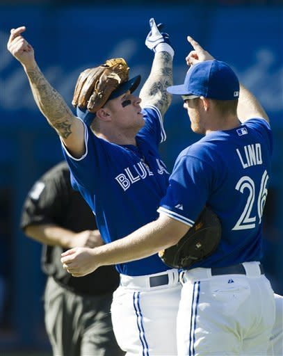 Toronto Blue Jays third baseman Brett Lawrie, left, celebrates with teammate Adam Lind, right, after defeating the Boston Red Sox 5-0 in a baseball game in Toronto on Sunday, Sept. 16, 2012. (AP Photo/The Canadian Press, Nathan Denette)