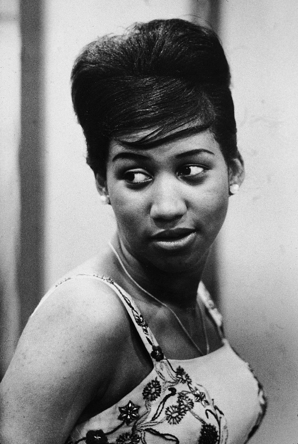 <p>Aretha Franklin looks over her shoulder, with her hair pulled up into a beehive style. Franklin was the first woman to be inducted into the Rock and Roll Hall of Fame. (Photo: Getty Images) </p>