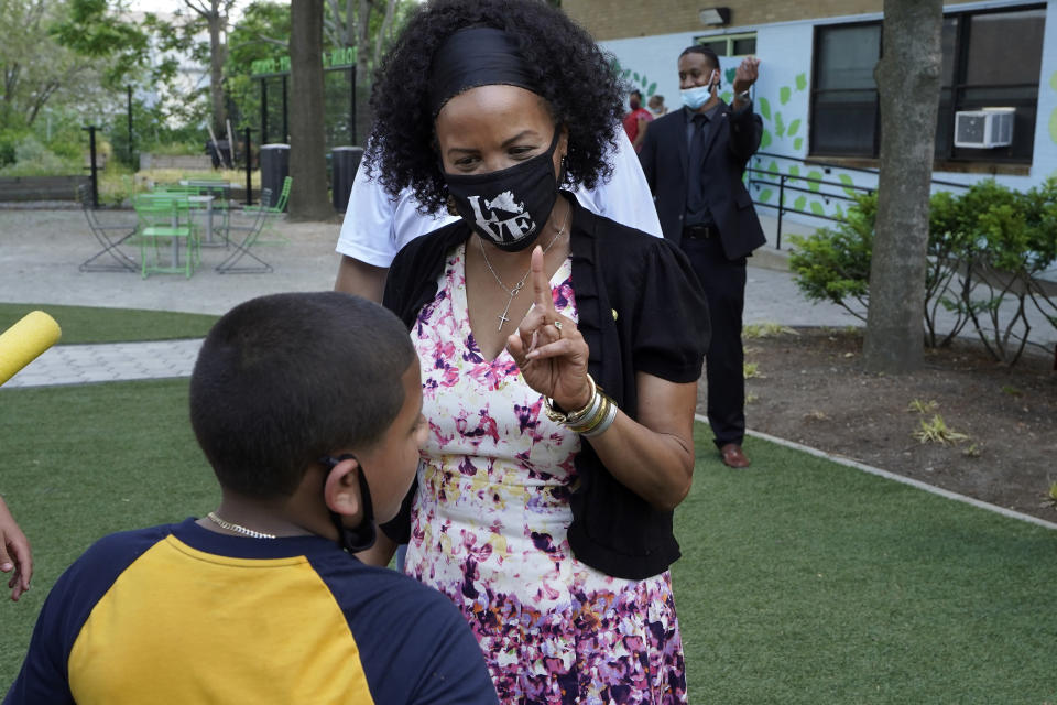 """Acting Boston Mayor Kim Janey speaks with a young person while visiting the Tobin Community Center, Tuesday, June 8, 2021, in Boston. The chair of the Boston School Committee, Alexandra Oliver-Dávila, resigned amid criticism of racially charged texts she shared with another member of the committee disparaging families of students, city officials announced Tuesday, June 8. Janey said in a written statement Tuesday that the texts were """"unfortunate and unfairly disparaged members of the Boston Public Schools community."""" (AP Photo/Steven Senne)"""