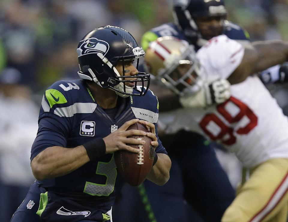 Seattle Seahawks' Russell Wilson looks to pass during the first half of the NFL football NFC Championship game against the San Francisco 49ers Sunday, Jan. 19, 2014, in Seattle. (AP Photo/Marcio Jose Sanchez)