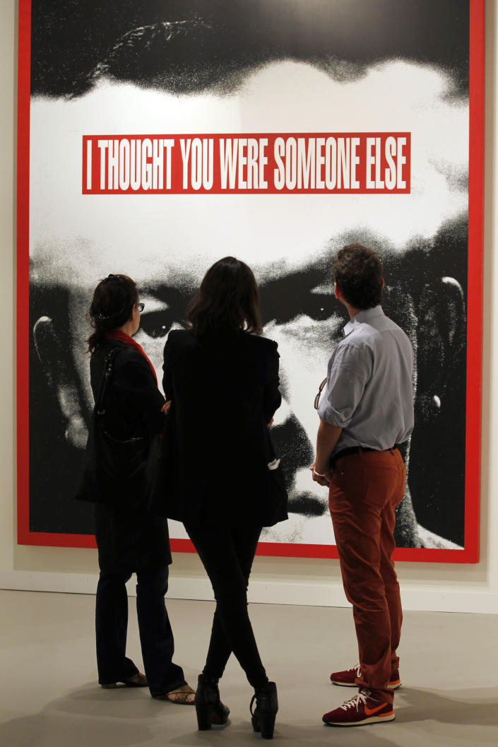 """FILE - This Dec. 5, 2012 file photo shows a group of people look at a large work by Barbara Kruger """"Untitled (I Thought You Were Someone Else)"""" on display as part of Art Basel Miami Beach in Miami Beach, Fla. The 2013 Art Basel Miami Beach takes place Dec. 5-8. (AP Photo/Wilfredo Lee, File)"""
