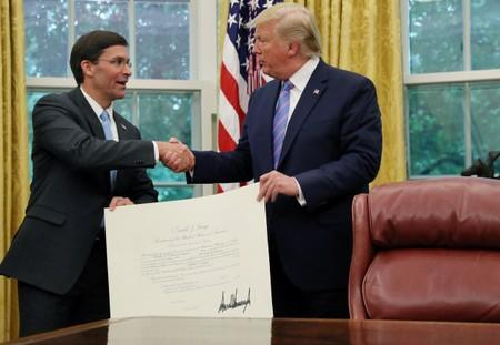 U.S. President Donald Trump shakes hands with Mark Esper after Esper was sworn in as the new Secretary of Defense while they hold a certificate recognizing the appointment in the Oval Office of the White House