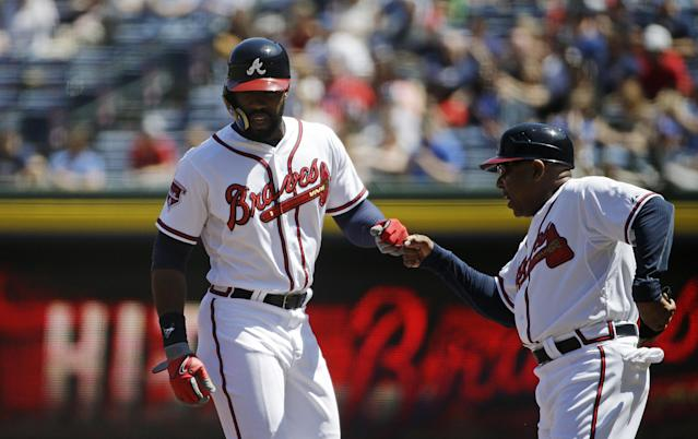 Atlanta Braves' Jason Heyward, left, is fist-bumped by first base coach Terry Pendleton after hitting a single in the first inning of a baseball game against the Miami Marlins, Wednesday, April 23, 2014, in Atlanta. (AP Photo/David Goldman)