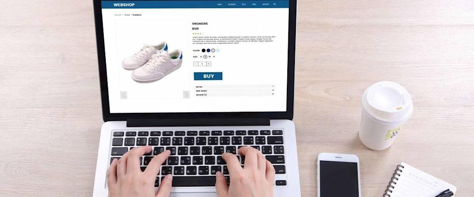 Top view business woman buying sneakers on ecommerce website with smart phone and coffee on wooden desk
