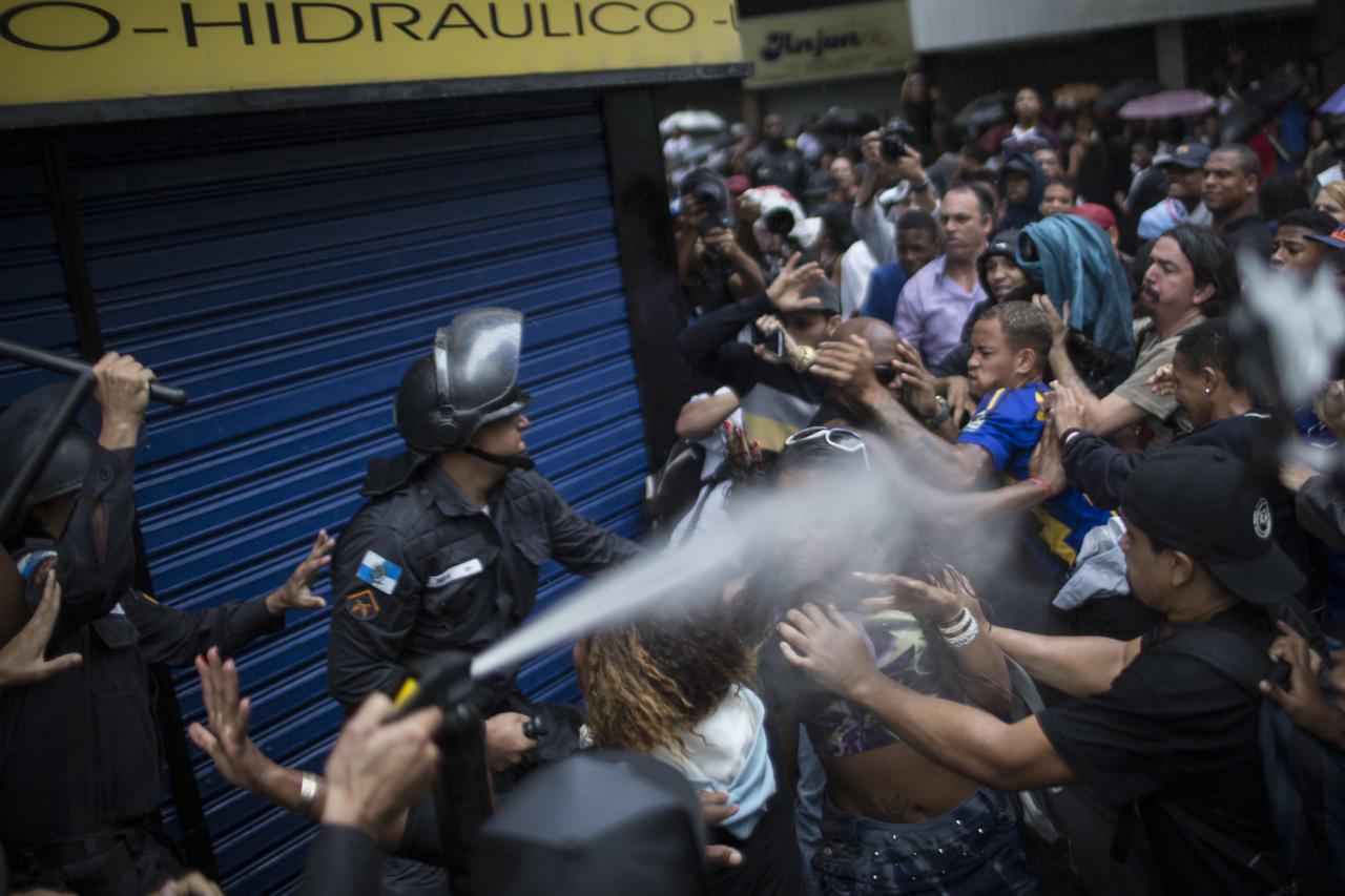 A woman is pepper sprayed as residents of Pavao-Pavaozinho slum clash with riot police during a protest against the death of Douglas Rafael da Silva Pereira after his burial in Rio de Janeiro, Brazil, Thursday, April 24, 2014. A protest followed the burial of Douglas Pereira, whose shooting death sparked clashes Tuesday night between police and residents of the Pavao-Pavaozinho slum. (AP Photo/Felipe Dana)