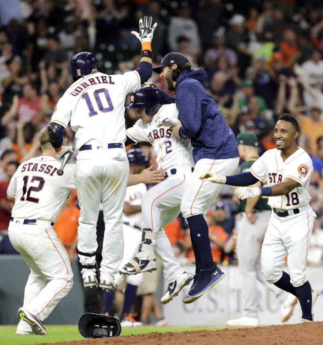 Houston Astros' Alex Bregman (2) celebrates with teammates after hitting a ground ball to Oakland Athletics catcher Jonathan Lucroy to score Kyle Tucker during the 11th inning of a baseball game Tuesday, July 10, 2018, in Houston. The Astros won 6-5. (AP Photo/David J. Phillip)