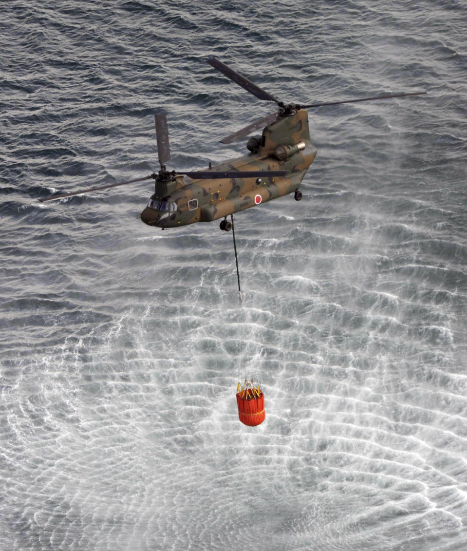 <p>A Japan Air Self-Defense Force CH-47 Chinook helicopter collects water from the ocean to drop on the reactors at the Fukushima Daiichi nuclear plant in Fukushima March 17, 2011. REUTERS/Yomiuri</p>