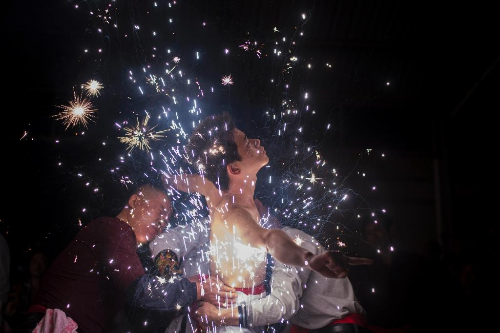 The 'eating flowers' ritual involves leaning bare chested into fireworks that spit out white sparks (AFP Photo/Johannes EISELE)