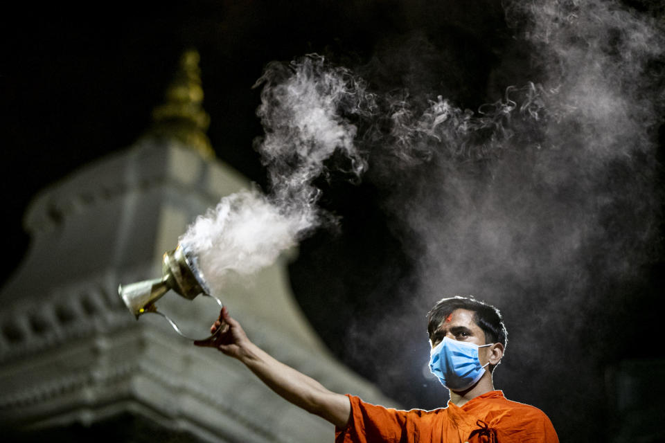 A Nepalese Hindu priest wearing face mask as a precaution against the coronavirus performs evening rituals at Pashupatinath Hindu temple in Kathmandu, Nepal, Monday, April 19, 2021. (AP Photo/Niranjan Shrestha)