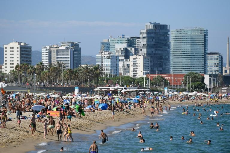 People swim and sunbathe at Bogatell beach in Barcelona, one of the several beaches that had to be closed due to overcapacity