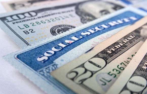A Social Security card wedged between a fanned pile of cash bills.