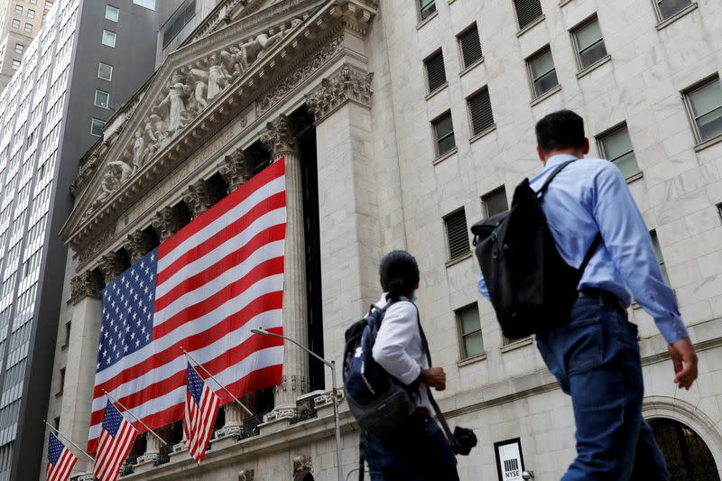 People walk by the New York Stock Exchange (NYSE) in Manhattan, New York City