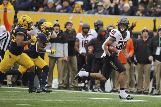 Oklahoma State running back Chuba Hubbard (30) looks down field on a long run against West Virginia the first half of an NCAA college football game in Morgantown, W.Va., on Saturday, Nov. 23, 2019. (AP Photo/Chris Jackson)