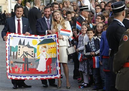 Luxembourg's Hereditary Grand Duke Guillaume (C) and his wife Countess Stephanie de Lannoy (R) pose with a drawing received as presents from children besides Luxembourg's mayor Xavier Bettel (L), as they leave the Luxembourg city hall after their civil wedding service in Luxembourg October 19, 2012. REUTERS/Vincent Kessler