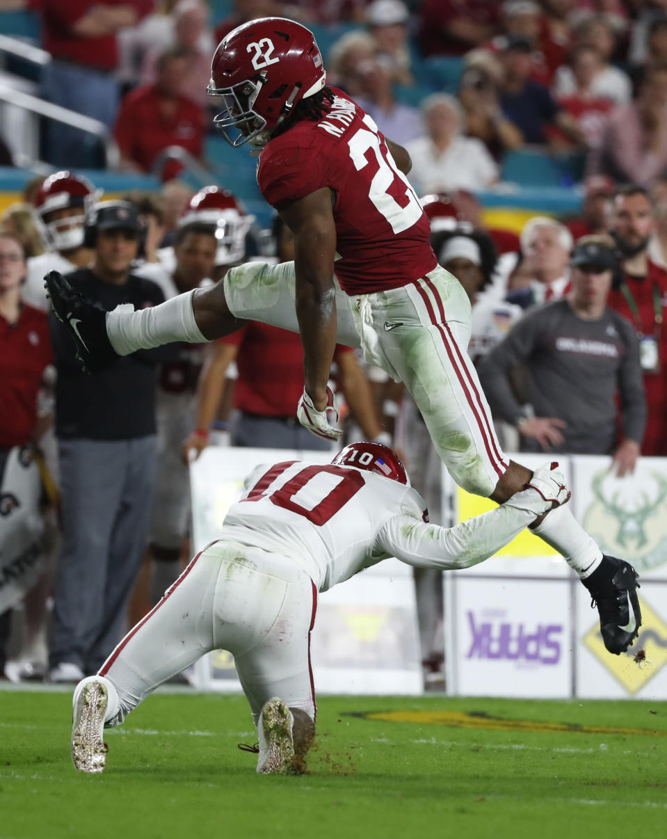 Alabama running back Najee Harris (22) jumps over Oklahoma safety Patrick Fields (10), during the first half of the Orange Bowl NCAA college football game, Saturday, Dec. 29, 2018, in Miami Gardens, Fla. (AP Photo/Wilfredo Lee)