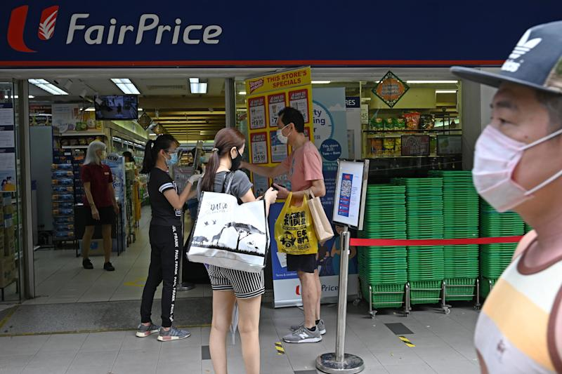 People waiting to enter a supermarket have their identity documents checked by staff before they can enter the premises, as a protective measure against the spread of the COVID-19 novel coronavirus, in Singapore on May 2, 2020. (Photo by Roslan RAHMAN / AFP) (Photo by ROSLAN RAHMAN/AFP via Getty Images)