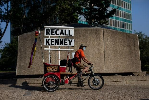 A man rides with a Recall Kenney sign during a protest in support of COVID-19 health orders in Edmonton. (Jason Franson/Canadian Press - image credit)