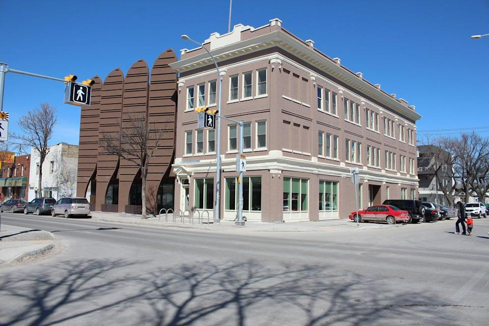 A three-storey building on a city corner seen from front and side angle.