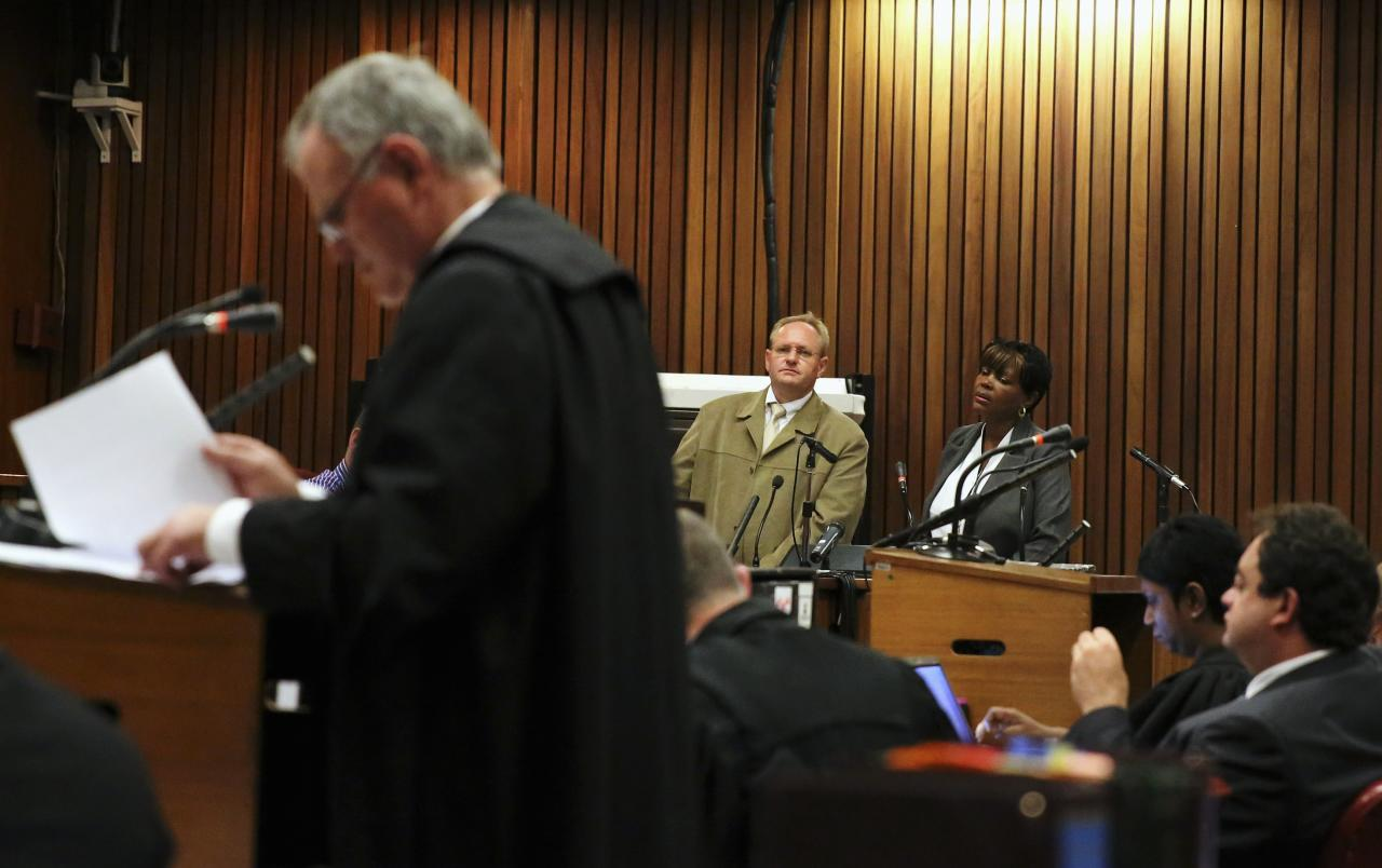 Police photographer Bennie van Staden (C) testifies as Barry Roux (L), lawyer for Olympic and Paralympic track star Oscar Pistorius, goes through his notes during the trial for the murder of Oscar's girlfriend Reeva Steenkamp, at the North Gauteng High Court in Pretoria, March 17, 2014. Pistorius is on trial for murdering his girlfriend Reeva Steenkamp at his suburban Pretoria home on Valentine's Day last year. He says he mistook her for an intruder. REUTERS/Siphiwe Sibeko (SOUTH AFRICA - Tags: CRIME LAW SPORT ATHLETICS)