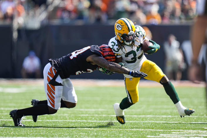 Green Bay Packers running back Aaron Jones (33) is pushed out-of-bounds by Cincinnati Bengals safety Vonn Bell (24) in the first half of an NFL football game in Cincinnati, Sunday, Oct. 10, 2021. (AP Photo/AJ Mast)