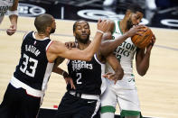 Boston Celtics forward Tristan Thompson, right, grabs a rebound next to Los Angeles Clippers forwards Kawhi Leonard (2) and Nicolas Batum (33) during the first half of an NBA basketball game Friday, Feb. 5, 2021, in Los Angeles. (AP Photo/Marcio Jose Sanchez)