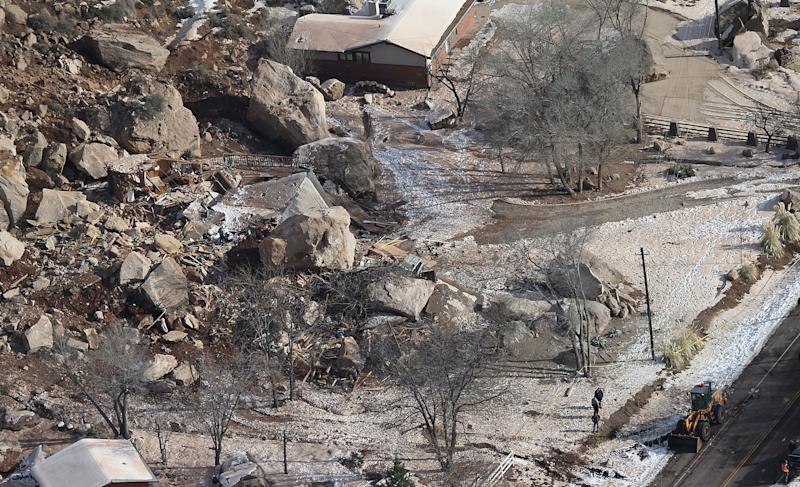 FILE - In this Dec. 13, 2013, file photo,officials survey the boulders from a rock slide that crushed a home and killed two people, in Rockville, Utah. Geologists are warning of the possibility of more rock slides in Utah like one in December that killed a middle-aged couple, flattening their cliff-side home near Zion National Park. The Utah Geological Society released its report Thursday, April 3, 2014, saying a massive sandstone slab near the one dislodged by rain and snow in December now threatens to crash and shatter onto the slope below. Officials say boulders could then crush a string of homes in Rockville, about 250 miles south of Salt Lake City. (AP Photo/The Deseret News, Tom Smart, File) SALT LAKE TRIBUNE OUT; MAGS OUT