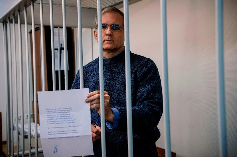 Paul Whelan holds a message as he stands inside a defendants' cage before his latest hearing in Moscow: AFP/Getty