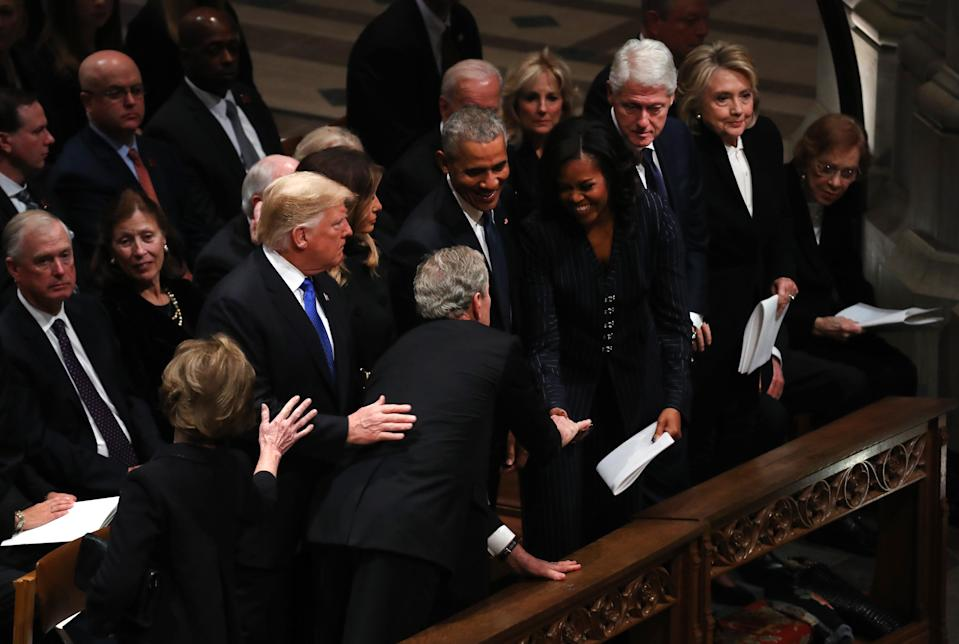 Former President George W. Bush and Michelle Obama had another sweet moment, this time at his father's funeral. (Photo: Andrew Harrer/Bloomberg via Getty Images)