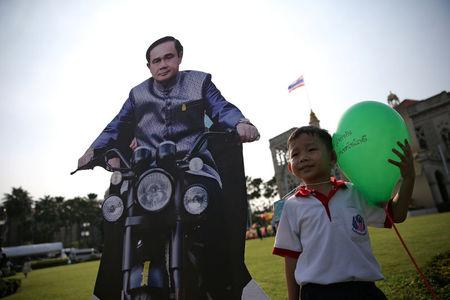 A boy poses next to a cardboard cut-out of Thailand's Prime Minister Prayuth Chan-ocha during preparations for national Children's Day at Government House in Bangkok, Thailand, January 12, 2018. REUTERS/Athit Perawongmetha
