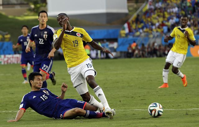 Japan's Yasuyuki Konno fouls Colombia's Adrian Ramos to give away a penalty during the group C World Cup soccer match between Japan and Colombia at the Arena Pantanal in Cuiaba, Brazil, Tuesday, June 24, 2014. (AP Photo/Thanassis Stavrakis)