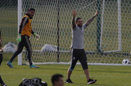 FILE - In this June 12, 2018 file photo, Colombian singer Maluma, right, gestures next to Mexico goalkeeper Jose de Jesus Corona, left, at the end of a training session of the Mexico national soccer team at the World Cup in Moscow. Russian police say that $800,000 worth of valuables have been stolen from Malumas hotel room in Moscow while hes visiting Russia to support the Colombia team at the World Cup. (AP Photo/Eduardo Verdugo, File)
