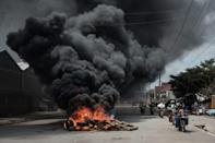 <p>Motorcyclists pass a burning tyre barricade following a demonstration by Kenyan opposition party National Super Alliance (NASA) supporters on Nov. 17, 2017 in Nairobi. (Photo: Yasuyoshi Chiba/AFP/Getty Images) </p>