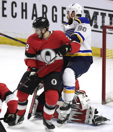 The puck hits the pad of Ottawa Senators goaltender Anders Nilsson (31) as Senators defenseman Cody Goloubef (28) defends against St. Louis Blues center Ryan O'Reilly (90) during first-period NHL hockey game action in Ottawa, Ontario, Thursday March 14, 2019. (Justin Tang/The Canadian Press via AP)