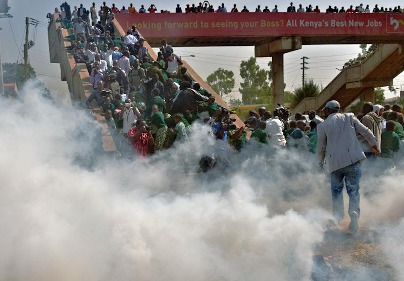 Children from the Lang'ata Road school scramble up a bridge to escape tear gas after police attempted to break up their demonstration against the removal of their school's playground (AFP Photo/Tony Karumba)