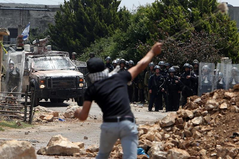 A Palestinian protester hurls a stone towards Israeli forces during clashes in the West Bank village of Kfar Qaddum on May 15, 2015 (AFP Photo/Jaafar Ashtiyeh)