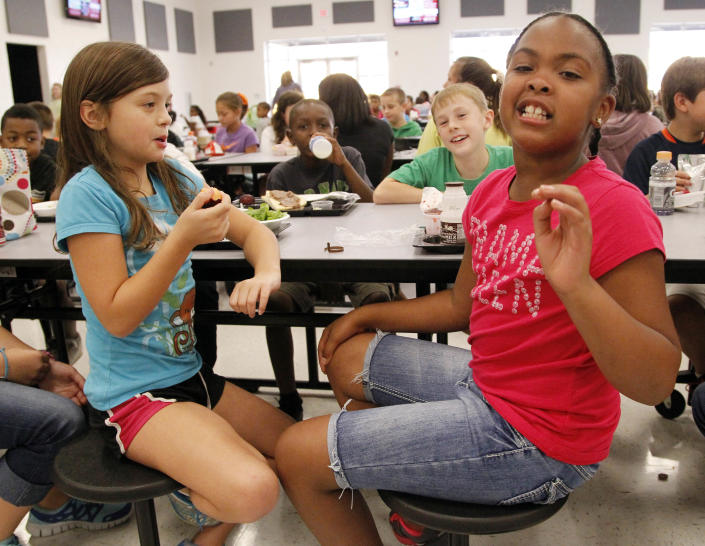 Eastside Elementary school fourth grader Raela Bridges, nine, right, explains what parts of the school lunch she likes to her classmates Grace Bethany, left, Cameron Kinard, back left, and Brock Maddox, back right, all nine, Wednesday, Sept. 12, 2012 in Clinton, Miss. While much consideration goes into the planning of these school children's lunches, the children have their own strong opinions about what items they prefer to eat. (AP Photo/Rogelio V. Solis)