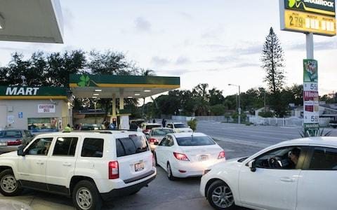 Vehicles sit lined up waiting to get fuel from a gas station ahead of Hurricane Irma in Miami - Credit: Bloomberg