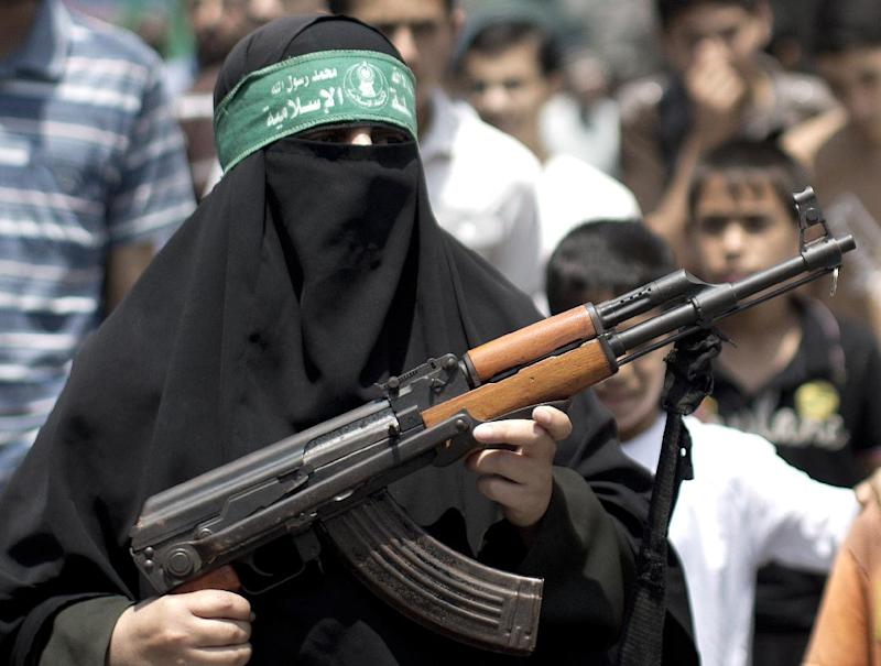 A Palestinian woman holds up a rifle during a protest in Gaza on July 4, 2014 against the kidnapping and killing a Palestinian teenager by Israeli settlers in Jerusalem