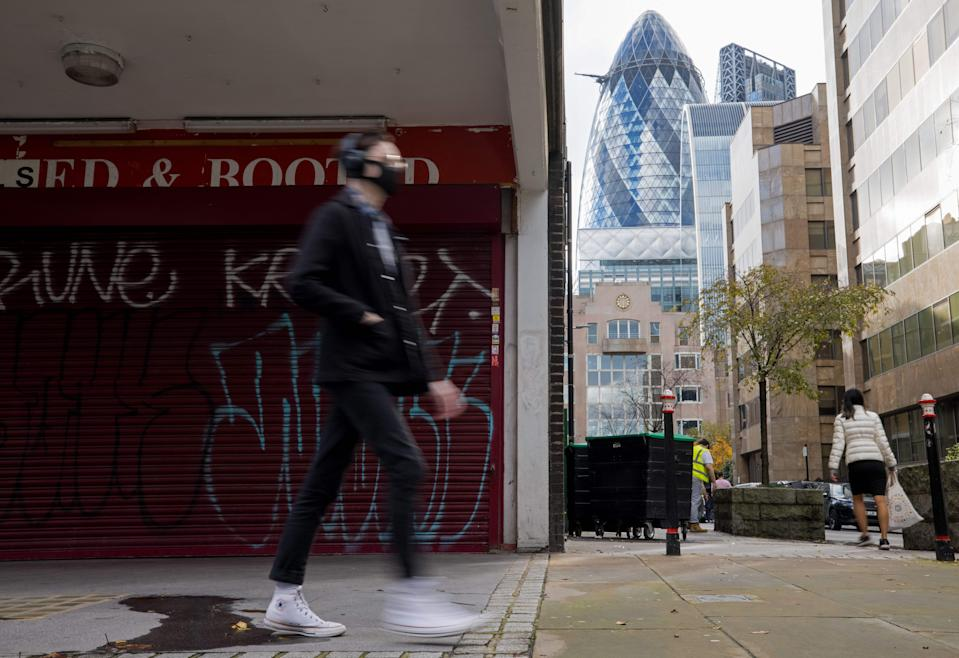 A man wearing a protective face covering to combat the coronavirus walks past a closed shop in central London on November 10, 2020. - Britain's unemployment rate has jumped to 4.8 percent as the coronavirus pandemic destroys a record number of UK jobs, official data showed Tuesday. (Photo by Tolga Akmen / AFP) (Photo by TOLGA AKMEN/AFP via Getty Images)