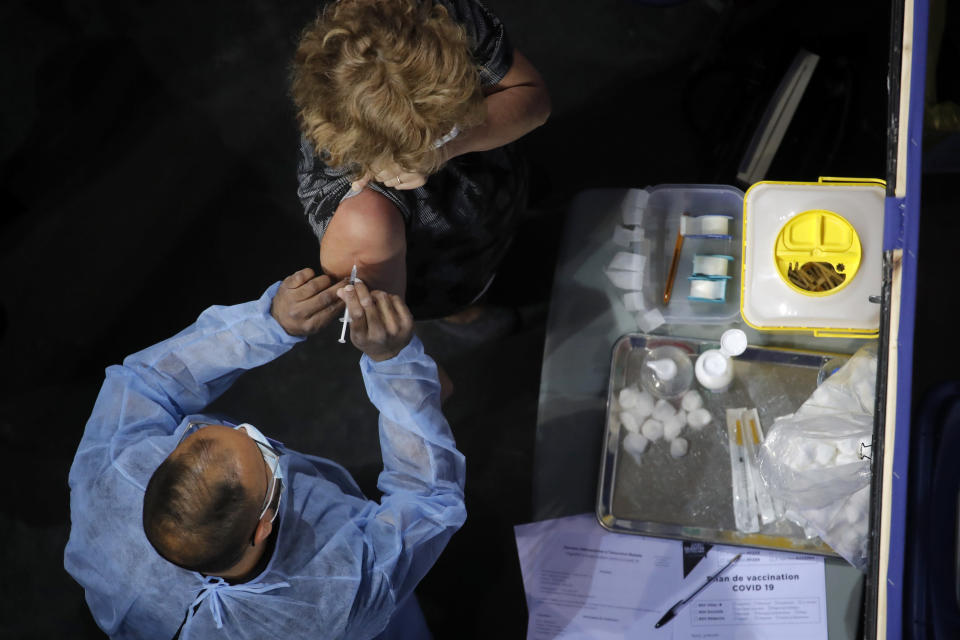 """FILE - In this March 29, 2021 file photo, a woman receives Pfizer's COVID-19 vaccine at the National Velodrome in Saint-Quentin-en-Yvelines, west of Paris. Social media influencers in France with hundreds of thousands of followers say a mysterious advertising agency offered to pay them if they agreed to smear Pfizer's COVID-19 vaccine with negative fake stories. The smear effort drew a withering response from French Health Minister Olivier Veran, who called it """"pathetic."""" (AP Photo/Christophe Ena, File)"""